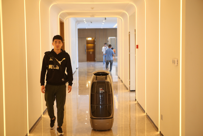 """来了,阿里首家未来酒店实体店终于要来了!近日,飞猪官宣称,阿里首家未来酒店被命名为""""FlyZoo Hotel"""",中文名字是""""菲住布渴""""。 据称,这是全球第一家支持全场景刷脸住宿的酒店,从入住登记、客房体验及退房流程,全程实现AI智能化服务。 机器人前台服务、机器人送餐和客房智能控制,在传统酒店的智能化改造中已经有很多的案例,包括万豪等国际品牌酒店都在尝试。而像""""菲住布渴""""酒店一样,甚至没了传统酒店的前台,实现智能的系统化解决方案,还是首次出现。 以至于业内惊呼,阿里是要真正要革传统酒店的命,是要让传统酒店人失业。更有声音认为,客人全程依赖机器人等高科技,是一种冷冰冰的体验。 阿里则不这么认为。 首先,未来酒店是要帮助到整个酒店行业。通过酒店管理平台系统能力的提升,未来酒店的人效比是传统同档次、同等规模酒店的1.5倍。通过这一整套酒店系统的数字化、智能化解决方案,阿里巴巴为酒店装上智慧大脑。这也正是阿里巴巴一直强调赋能行业的又一次新尝试,未来这些沉淀下的能力将可能赋能到酒店业的其他公司。 其次,在以具有引领性的科技打造智能化体验之后,阿里未来酒店将目光落于提升服务温度,对未来酒店中人的服务属性重新调整和定义。 在未来酒店场景内,服务人员担任着不同的使命和职责,为住客提供专属个性化服务,着重住客问题的支持和解决。比如,大堂中的服务大使可以帮助住客解决机器人和系统替代不了的问题,或者给一些不想使用智能的住客给予服务。 在阿里看来,智能系统和服务机器人旨在淘汰简单、重复性劳动,提升酒店服务整体效率,为消费者带来一些科技福利,而真正能够推进旅游业迭代的是切实服务,包括酒店场景中人的服务意识、服务水平全面升级,始终坚持将人放在第一位,体验绝不会是""""冰冷""""的。 未来的酒店不一定无人。""""人工智能不是万能的,但是没有人是万万不能的"""",阿里未来酒店CEO王群指出,未来酒店的人工智能化解决方案,提升的是酒店运营、管理系统的效率;在酒店的服务中,人仍然是不可或缺的重要组成部分。现在,阿里未来酒店也在聚焦于更有温度的消费者体验,为旅行服务升级的""""最后1公里""""积蓄力量。 未来酒店的人工智能并非仅仅提供用户黑科技般炫酷的体验,其背后更是改造传统酒店运营管理中的低效率环节,让酒店的后台管理更加的智能以缩减低效率环节的人工成本,在替代部分人工服务的同时,更有效地为包括面对面服务在内的精细化、个性化服务提供各种支撑。 服务和效率的结合在订房伊始就开始体现:客人在订房时就可以根据自己的需求和喜好在APP上进行选房甚至选床,在服务端这是个性化服务体验,在运营端,则淘汰了传统的前台服务人员人工查房态、排房。 在check-in和退房环节,服务体验与运营效率提升更明显:客人可以在手机APP上或在大堂自助办理check-in,省去排队等待的时间,完全取代了前台人工查房态、排房、办理押金和房卡等人工环节;退房时,只需在APP上进行操作,核对消费账单后即可确认离店,无须等待查房、结算。 对客人而言,一个比较酷的体验是:通过全场景的身份识别,电梯、房间、餐厅、健身房等统统刷脸开门,借助无感体控定位系统,客人离开房间的瞬间,电梯也将自动响应等候;甚至在酒店餐厅,客人也无需等待结账或签单,用完餐就可以潇洒离去。 人工智能已经渗透到我们生活的方方面面,哪怕是从前需要人与人面对面交互的环节:餐厅的自助点餐和结账、电影票的预订和取票……这已经成为我们日程生活中的寻常体验。 """"菲住布渴""""就是集合了阿里经济体内多个团队的创新技术所打造的""""新物种""""。 人工智能智能提供冷冰冰的服务?直觉告诉我们,在阿里的这场生态布局下,是不存在的:不管是个人还是家庭,度假还是商务,阿里生态下的未来酒店,也许能给你想不到的温暖。 我们希望的未来的酒店或许是这样的: 打开APP开始预订酒店时,系统根据你的喜好和需求,将你喜好的房间推荐给你;当你抵达酒店的那一刻,你的管家(或者机器人)已经等候服务;无须多余的停留,不用刷房卡也不必记房号按楼层,你一路乘坐电梯直接进入房间;房间里的音乐、灯光,甚至电视播放的节目,都是已按你的喜好自动播放、调节;在你来之前,酒店服务员已按你以往住店时的喜好,为你准备好了可心的果盘、点心、饮料和夜床服务,一个足以打开你内心世界的暖心小礼品;智能管家还告诉你,餐厅新推出几款你可能喜欢的菜品…… 呃,如果你是女性,根据你自己在这家酒店(或这家品牌酒店的其他店)的经历,智能管家可能还会告诉你,这几天你可能需要红糖、热开水和定坤丹,管家都已为你准备好…… 惊不惊喜?意不意外?这才是有温度的服务。 未来酒店不是革传统酒店的命,也不是让酒店人失业,而是让传统酒店重生,让酒店人能更有温度地服务客人,服务于这个行业。"""